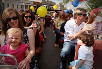 Families riding the double decker bus with ballons